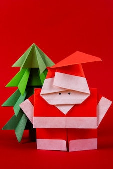 Close upnew year card handmade origami santa claus figures with trees. christmas concept winter crafted decorations studio shot