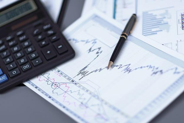 사업가 책상에 uppen 금융 차트 및 계산기를 닫습니다