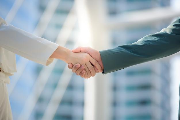 若いビジネスマンとアジアのビジネスウーマンのクローズアップ。ビジネスマンは握手