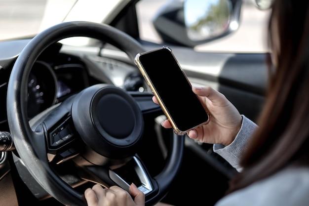 운전 중 운전대를 잡고 휴대전화를 사용하는 여성의 클로즈업, 운전 중 휴대전화 사용은 위험하고 불법입니다. 안전 운전 개념, 운전 중 휴대전화를 사용하지 마세요.