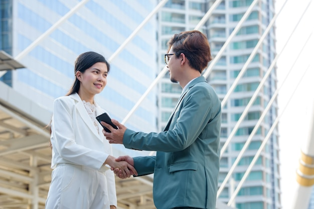 Close-ups of the young business man and the asian business woman hand in hand. business people shake hands