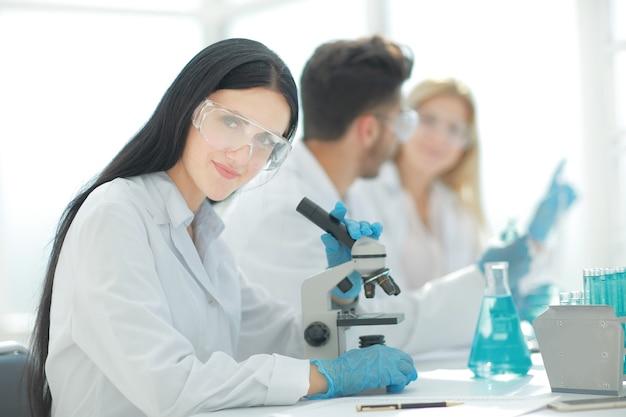 실험실 테이블에 앉아 upscientists 및 실험실 노동자를 닫습니다