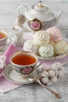 グレーの表面にセラミックカップ、シナモンスティック、綿の花で白いプレートにおいしいマシュマロで表示を閉じる、日曜日の朝の朝食。
