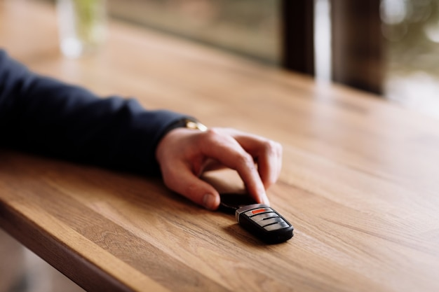 Close view of car keys put on the table by rich suited businessman in the cafe. coffee break in cafe or restaurant.