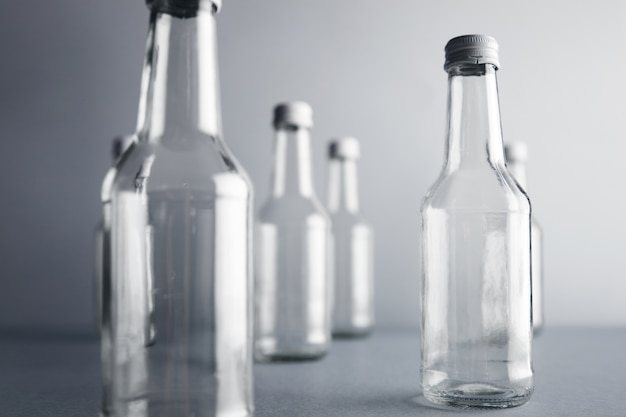 Close view on clear unlabeled empty glass bottles for cold beverages and drinks
