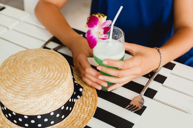 Крупным планом вид сверху руки привлекательной молодой женщины в соломенной шляпе, пьющей коктейль из тропического алкоголя на летних каникулах, сидя за столом в баре