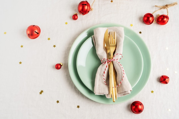 Close view of golden cutlery on light napkin for christmas table setting.