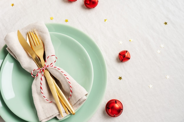 Close view of golden cutlery on light napkin for christmas table setting