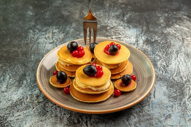 Close view of hands holding fork on fruit pancakes