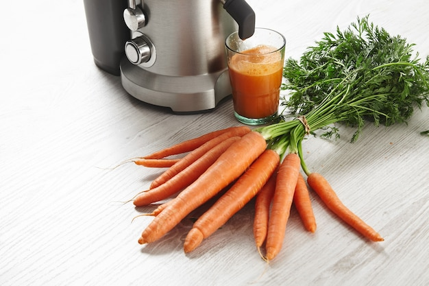 Close view metallic professional juicer with glass filled with tasty juice for breakfast from organic farm carrots lying on wooden table.