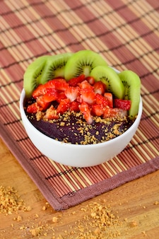 竹のテーブルナプキンにクリーミーなピーナッツ、キウイフルーツ、イチゴ、アサイーとアサイーボウルのビューを閉じる