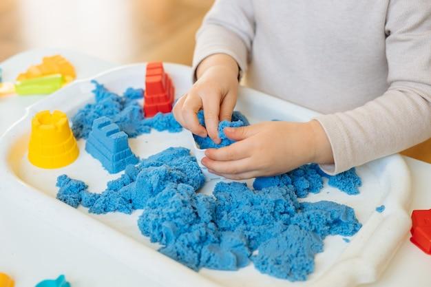 운동 모래를 가지고 노는 아이의 손보기를 닫습니다. 조기 발달 및 미세 운동 능력을위한 어린이 창의적인 게임입니다.