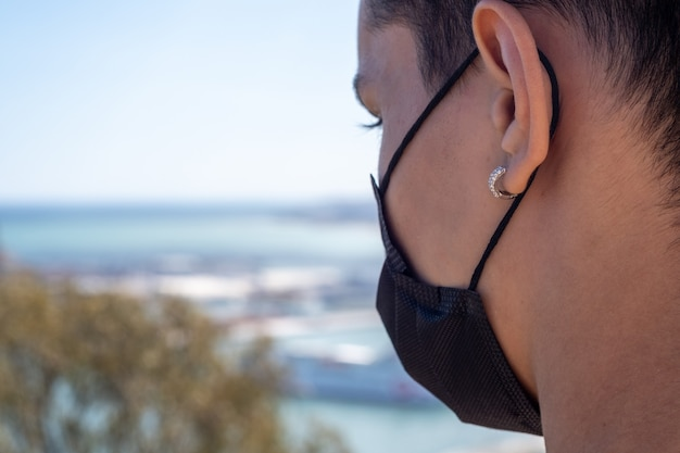 Крупным планом вид человека, использующего маску для лица с городом малага на заднем плане.