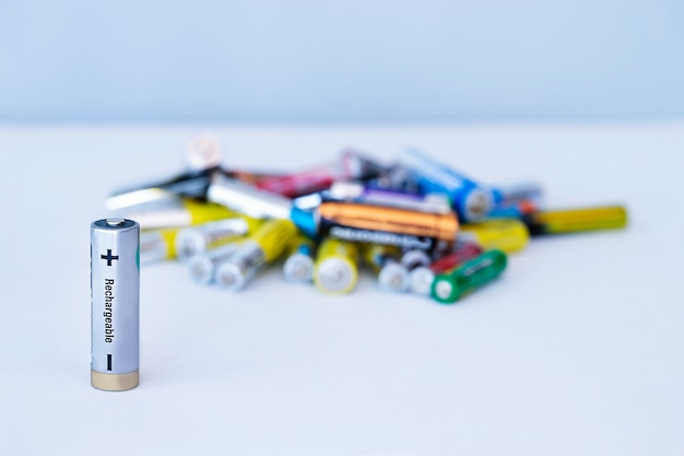 Крупным планом вид аккумуляторной батареи с кучей неперезаряжаемых батареек на расфокусированном фоне