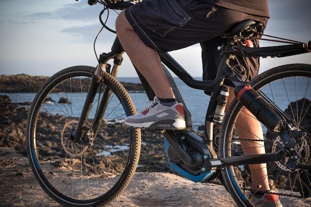電動自転車で崖の上に立っている年配の男性の足の拡大図。健康的なスポーツとライフスタイル。背景に青い海の水。