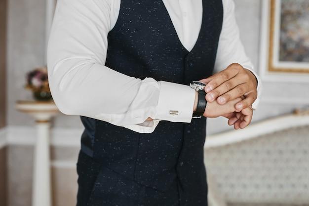 양복과 커프스 단추가 달린 셔츠를 입은 사업가의 손에 명품 시계의보기를 닫습니다.