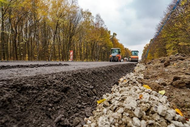 Близкий вид на ремонт дороги. каток работает на новой строительной площадке дороги