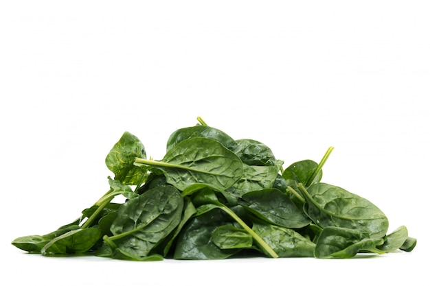 Close view of a pile of fresh spinach, isolated on a white background.
