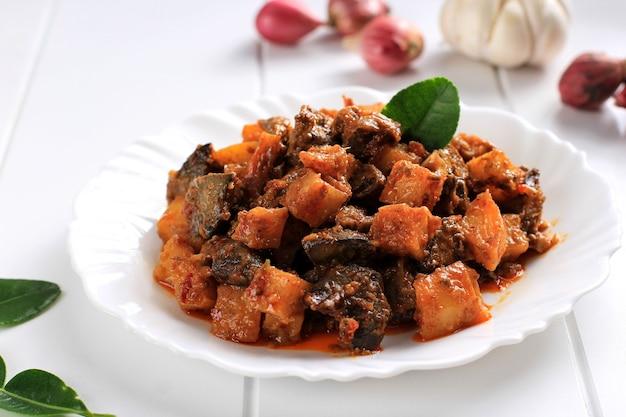 クローズビューsambalgoreng hati kentangまたはホットスパイシーなレバーとポテト、インドネシアの伝統的な料理、通常はケトゥパットとのイードアルフィトルのお祝いの間に提供されます。ホワイトプレートでお召し上がりいただけます