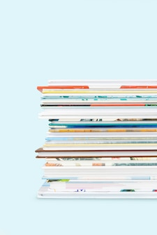 Close view of stack of children's books on a pastel blue background.