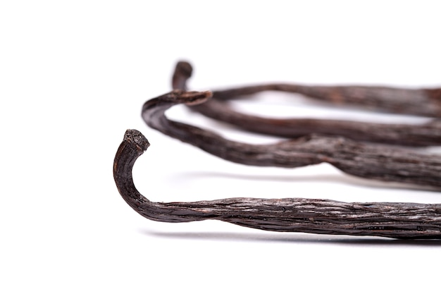Close view of vanilla pods over a white background.