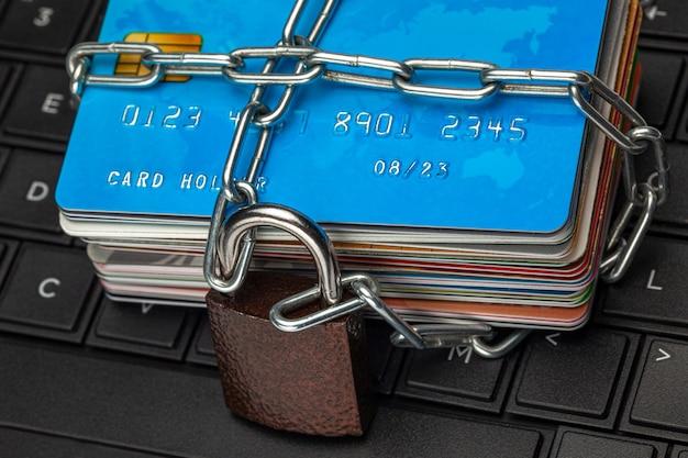 クレジットカードへのクローズドアクセスがロックをブロッククレジットカードのスタックとチェーン付きの南京錠