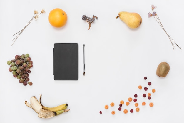 Closed black cover diary and pen surrounded with many fruits on white backdrop