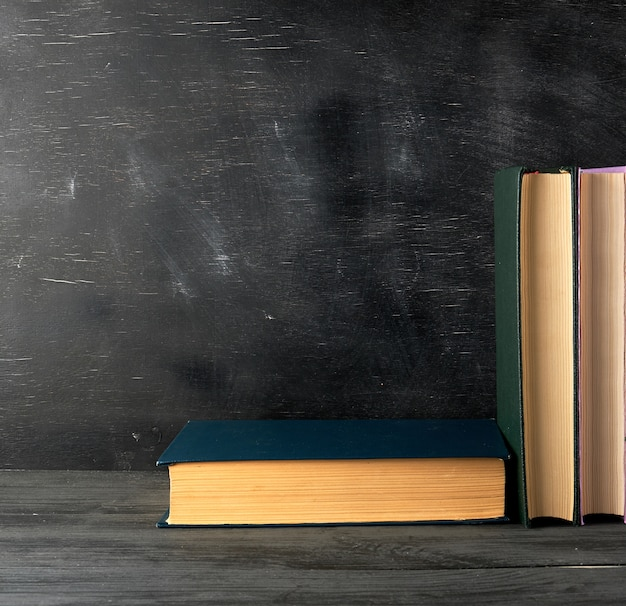 Closed books with yellow sheets on a black chalk board background