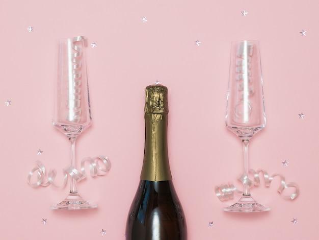 お祝いの背景にシャンパンの閉じたボトルと2つのグラス。シャンパングラスでお祭りの背景。