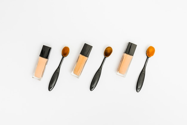 Closed bottles of liquid foundation with oval makeup brush on white background