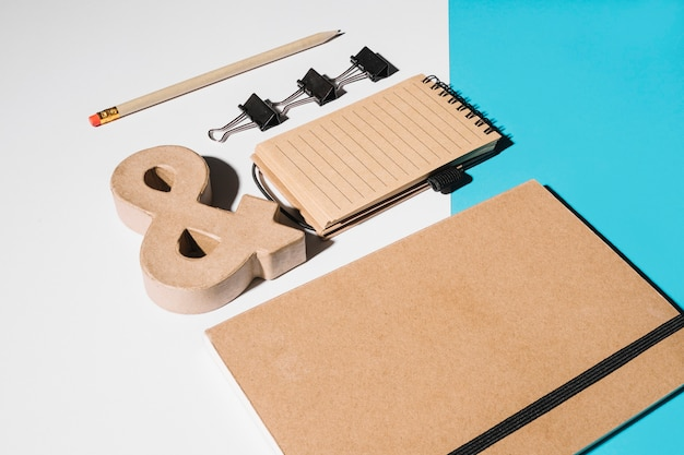 Closed brown cover notebook with wooden ampersand sign; bulldog clips and spiral notepad
