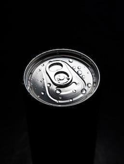 Закрытая банка газированного напитка с каплями на нем. освежает в летнюю жару. каникулярное настроение.