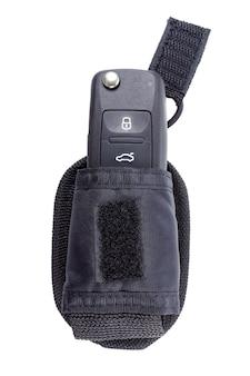 Закрытый ключ зажигания автомобиля в сумке для хранения на белом