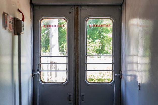 Закрытые двери в вестибюле поезда.