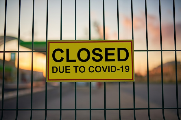 Closed due to covid-19 sign on a fence with blurred city view