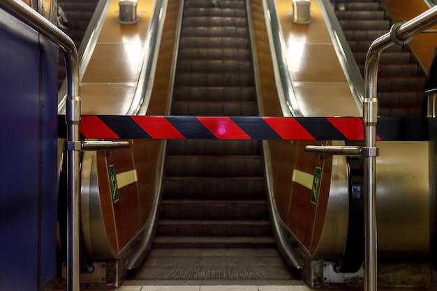 Закрытый эскалатор в метро. вид снизу. ремонт эскалаторов, вход закрыт, проезд закрыт. красные и черные полосы на непроницаемом барьере. эскалатор остановился. место для вашего лейбла и рекламы