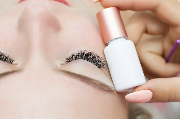 A closed eye with extended eyelashes and a tube of glue, primer next to it. glue for eyelash extensions. allergy.