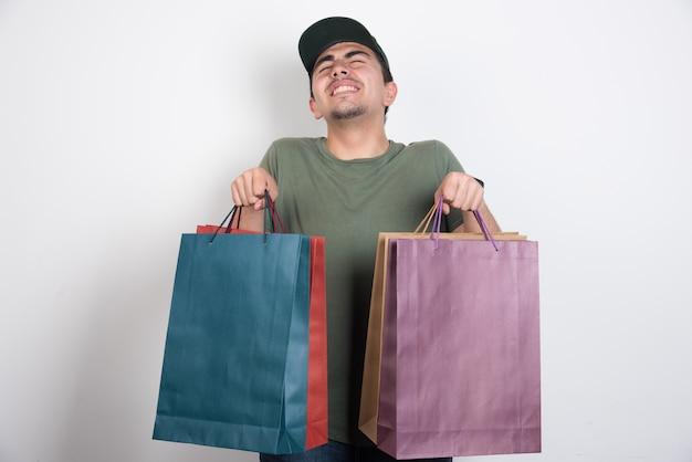 Uomo dagli occhi chiusi con borse della spesa su sfondo bianco.