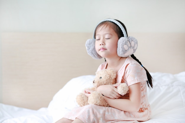 Closed eyes little asian child girl wearing winter earmuffs and embracing teddy bear while sitting on the bed at home.