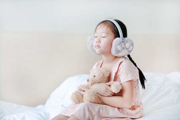Closed eyes little girl wearing winter earmuffs and embracing teddy bear while sitting on the bed at home.
