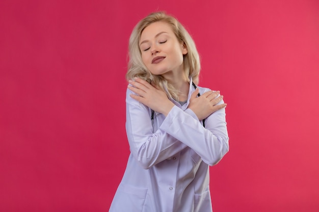 医療用ガウンで聴診器を身に着けている目を閉じた若い医者は、孤立した赤い背景に彼女の手を肩に置きました