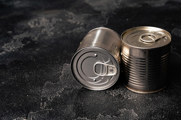 Closed food tin cans on dark background