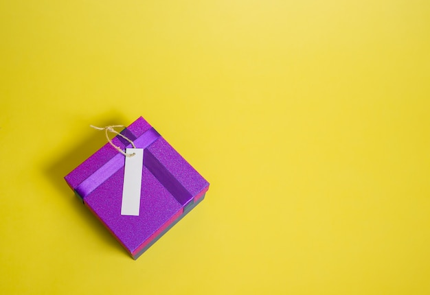 A closed gift box with an empty price tag on a yellow space. purple gift box. sale ads
