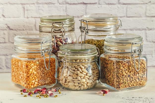 다양한 콩과 식물이 들어있는 닫힌 유리 병