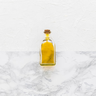 Closed glass oil bottle on two textured backdrop