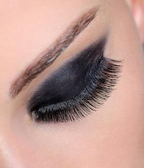 Closed human female eye with bright black eyeshadow and long false eyelashes