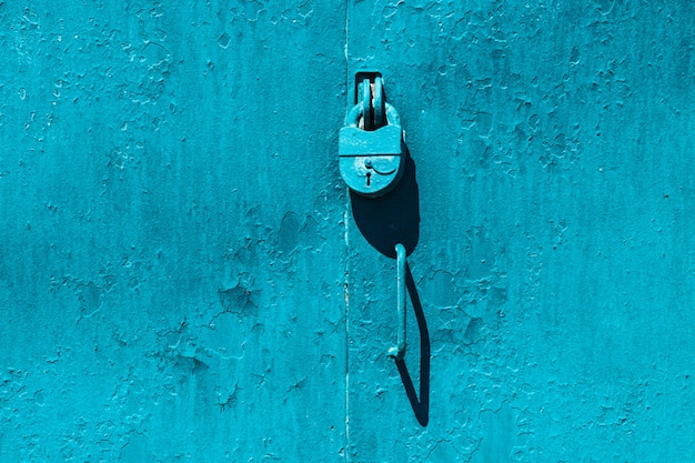 Closed imperfect blue garage gate with padlock close-up. texture of locked iron door with cyan peeling paint. flaky dye stains on grungy metal surface. textured background of rough faded steel gates.