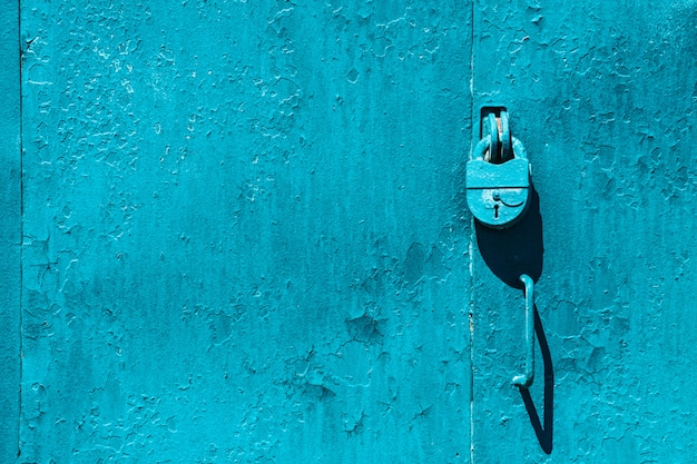Closed imperfect blue garage gate with padlock close-up.