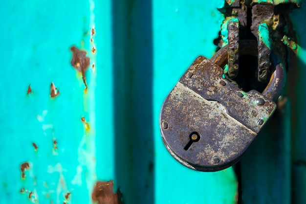 A closed iron lock on the irontattered graincracked door of an old country house old lock old castle...