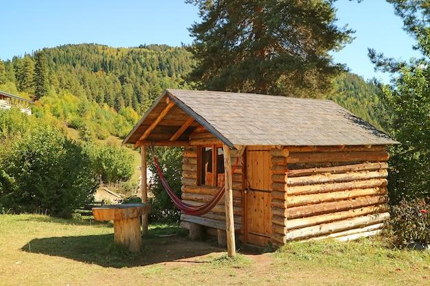 Закрытый бревенчатый домик на красивом склоне горы